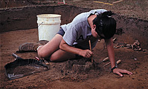 Graduate student carefully excavating the remains of a charred post